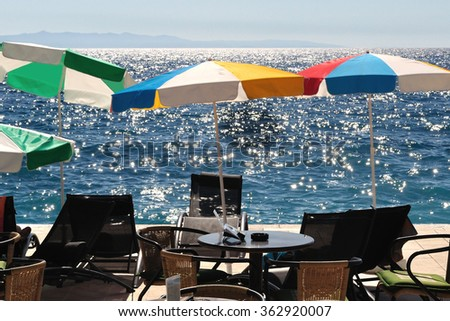 Colorful sunshades and beach chairs on the beach with sea in background. Podgora, Croatia - stock photo