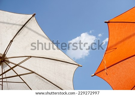 colorful sunshades umbrellas on a sunny summer day - stock photo