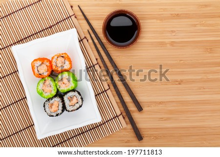 Colorful sushi maki with tobiko on bamboo table with copy space - stock photo
