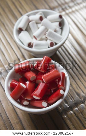 Colorful sweet in a white bowl over wooden table - stock photo