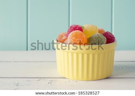 Colorful sweet jellies with sugar in a yellow classic white-ware baking bowl on a white wooden table with a robin egg blue background. Vintage look. - stock photo
