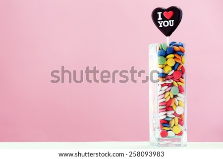 Colorful sweets with inscription in vase on table on color background - stock photo