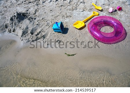 Colorful swim ring life buoy, bucket and shovels on the beach. - stock photo