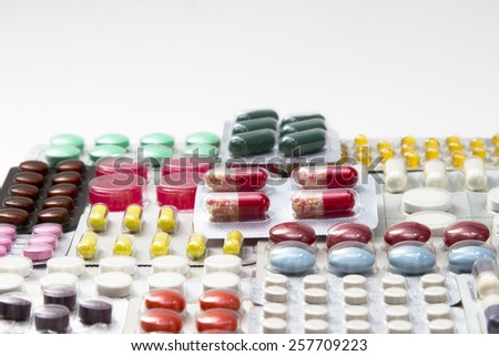 colorful tablets and capsules in blisters on white background - stock photo