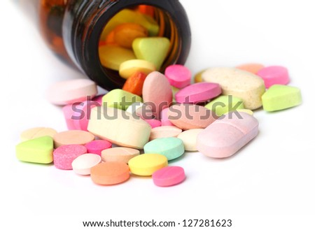 Colorful tablets spilled out bottles - stock photo