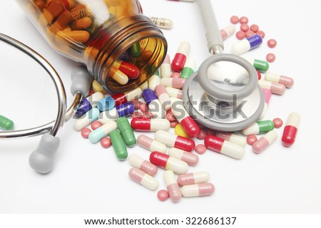 Colorful tablets with capsules and pills on white background - stock photo