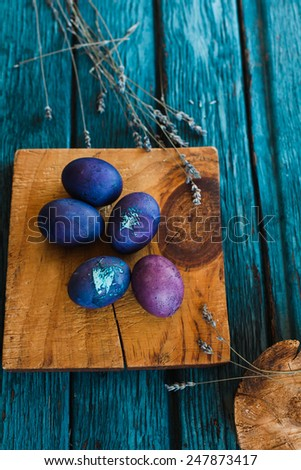 Colorful Textured easter Eggs with spring shoots an old aged scored blue wooden surface in a country kitchen. Rustic style  - stock photo