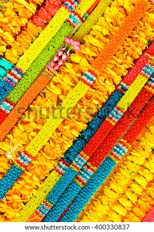 Colorful Thai garland, traditional flower decor, national ornament, Thailand, texture from garlands, symbol of Asia, asian background, yellow, red, blue and green colours, color decoration - stock photo