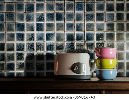 Colorful tiffin carrier and electric toaster on wooden cupboard in kitchen room against warm light - stock photo