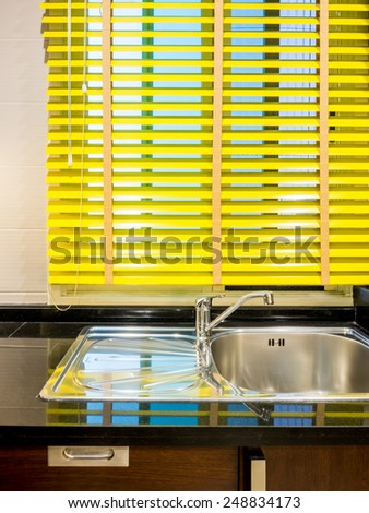 Colorful timber blind over sink in modern kitchen - stock photo