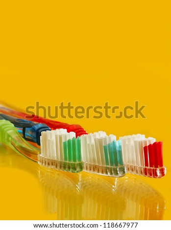Colorful tooth brush set on yellow counter top - stock photo