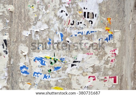 Colorful torn posters on grunge old walls - stock photo