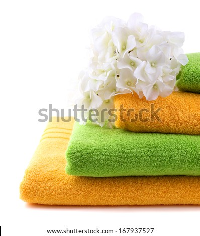 Colorful towels and flowers, isolated on white - stock photo
