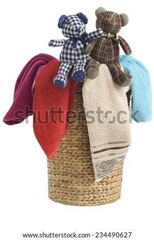 colorful towels in a basket isolated on white background and a resting teddy bears - stock photo