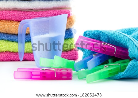 colorful towels, measuring cup filled with soap powder and clothes pegs isolated - stock photo