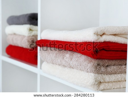 Colorful towels with wicker basket on shelf of rack background - stock photo