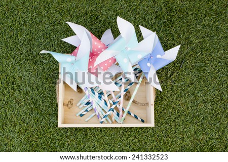 Colorful toy pinwheel against green grass background - stock photo