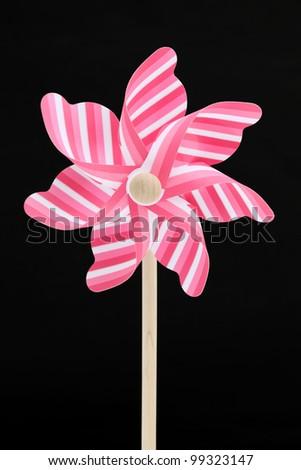 Colorful toy pinwheel on black background - stock photo