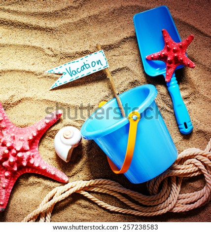 colorful toys for child sandboxes against the beach sand background/summer holidays background - stock photo