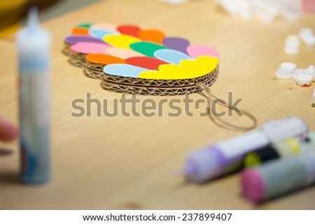 Colorful toys made of cardboard on a wooden table. Creative background - stock photo