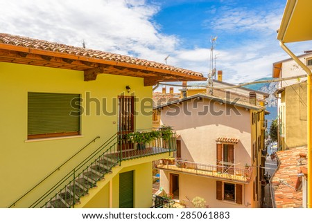 Colorful traditional Italian hotel balcony with view on old town and mountain lake - stock photo