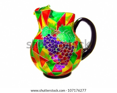 Colorful transparent stained glass grape drink pitcher / jug with a black handle and bottom - stock photo