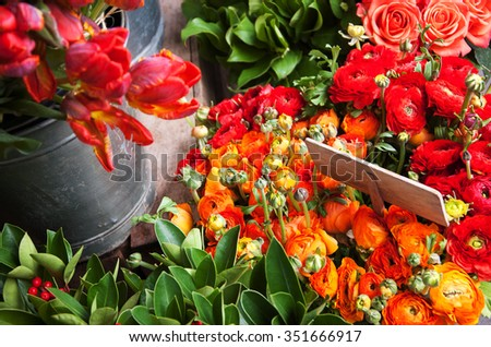 Colorful tulips and buttercups flowers with wooden price tag. Selective focus on buttercup flowers. - stock photo