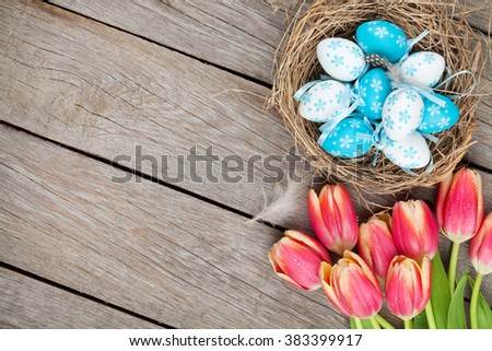 Colorful tulips and easter eggs in nest on wooden table. Top view with copy space - stock photo