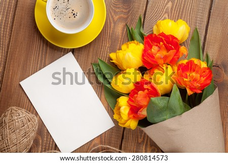 Colorful tulips bouquet, blank greeting card and coffee cup on wooden table - stock photo