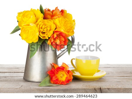 Colorful tulips bouquet in watering can and coffee cup on wooden table. Isolated on white background - stock photo