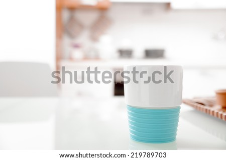 Colorful turquoise and white plastic cup on a kitchen counter in close up view with focus to the cup - stock photo