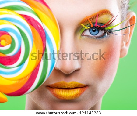 Colorful twisted lollipop, colorful fashion makeup - stock photo
