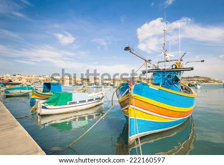 Colorful typical boats in Marsaxlokk - Mediterranean traditional fisherman village in the south east of Malta - stock photo