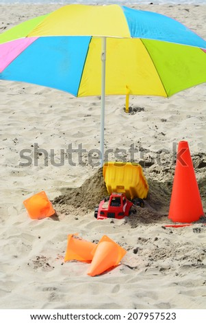 Colorful umbrella and children's toys in the sand at the beach. - stock photo