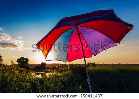 Colorful umbrella in the summer at sunset on a background of the sky - stock photo