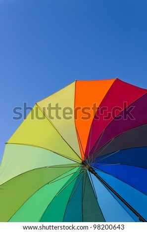 Colorful umbrella on a bright blue sky background, vertical view - stock photo