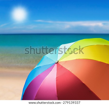 colorful umbrella on the beach background. Focus in the center of the umbrella - stock photo