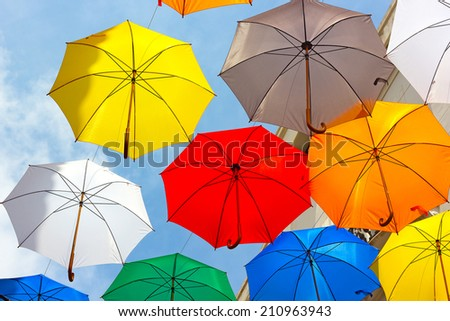 Colorful umbrellas against the sky in city settings. Umbrellas provide summer shade and attraction for shopping district. - stock photo