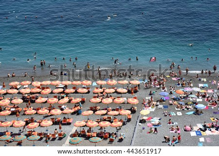 Colorful umbrellas and a stone beach in Positano, Italy, on the Amalfi Coast in Italy. - stock photo