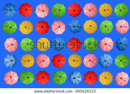 Colorful umbrellas floating magically in the sunny blue sky - stock photo