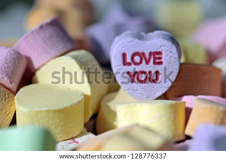 Colorful Valentine heart candy, focus on purple one with the words Love You on it. - stock photo