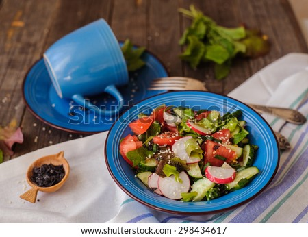 colorful vegetable fresh salad in blue dish over vintage background - stock photo