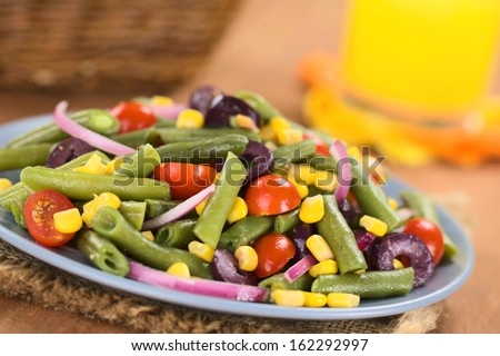 Colorful vegetarian salad made of green beans, cherry tomatoes, sweet corn, black olives and red onions on blue plate with orange juice in the back (Selective Focus, Focus one third into the salad)  - stock photo