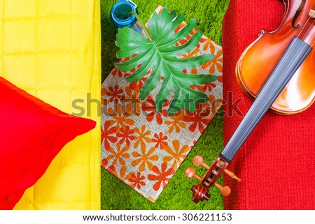 colorful & vibrant color of red stool, green carpet, yellow fabric seat, green leaf, red backrest pillow & violin for modern cozy living room interior & decoration - stock photo