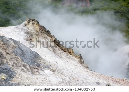 colorful volcanic land with hot steam behind colorful mineral sands - stock photo