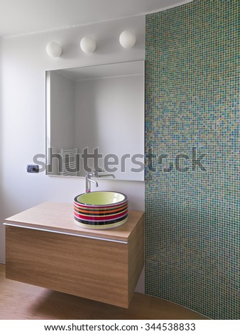 colorful washbasin on the natural wood furniture in the modern bathroom with a wall coated of mosaic tiles - stock photo