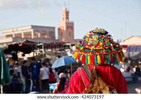 Colorful water bearer in Marrakech, Morocco. In the past, water bearers were men who brought some water with them to quench the thirst of people. To be easily recognizable they wore colorful dresses. - stock photo