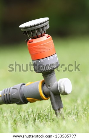 colorful water sprinkler in the grass - stock photo