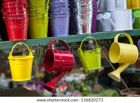 Colorful watering cans and buckets for plants at flower market in Paris. - stock photo