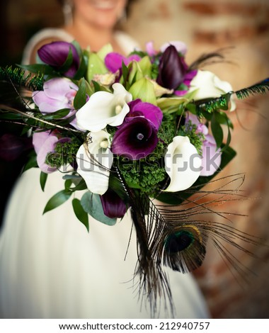 Colorful wedding bouquet with peacock feathers - stock photo